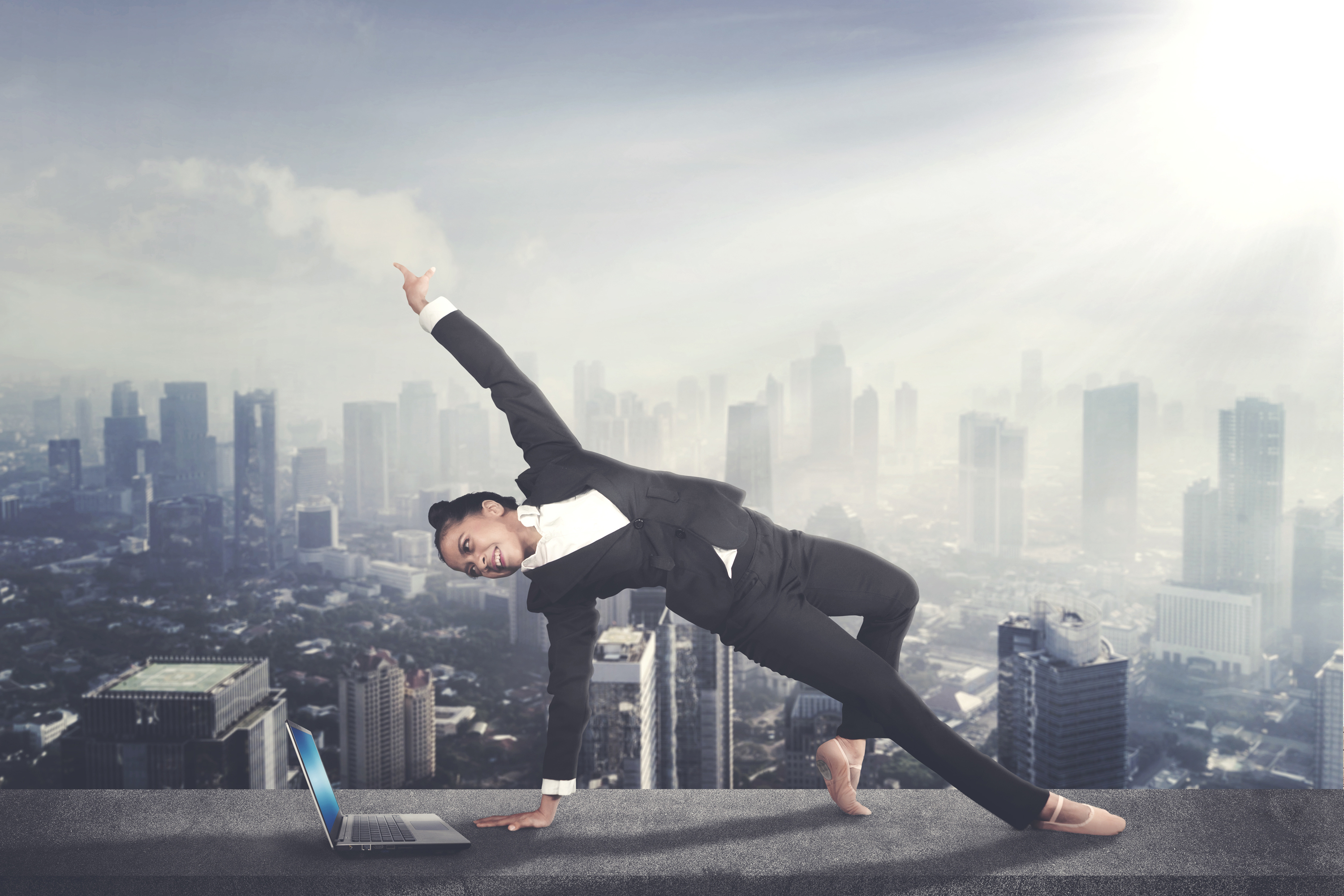 Image of female entrepreneur wearing ballet shoes while dancing with a laptop on the rooftop